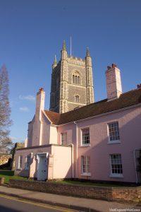 Roze huis in Dedham Suffolk met kerk op de achtergrond tegen een blauwe lucht